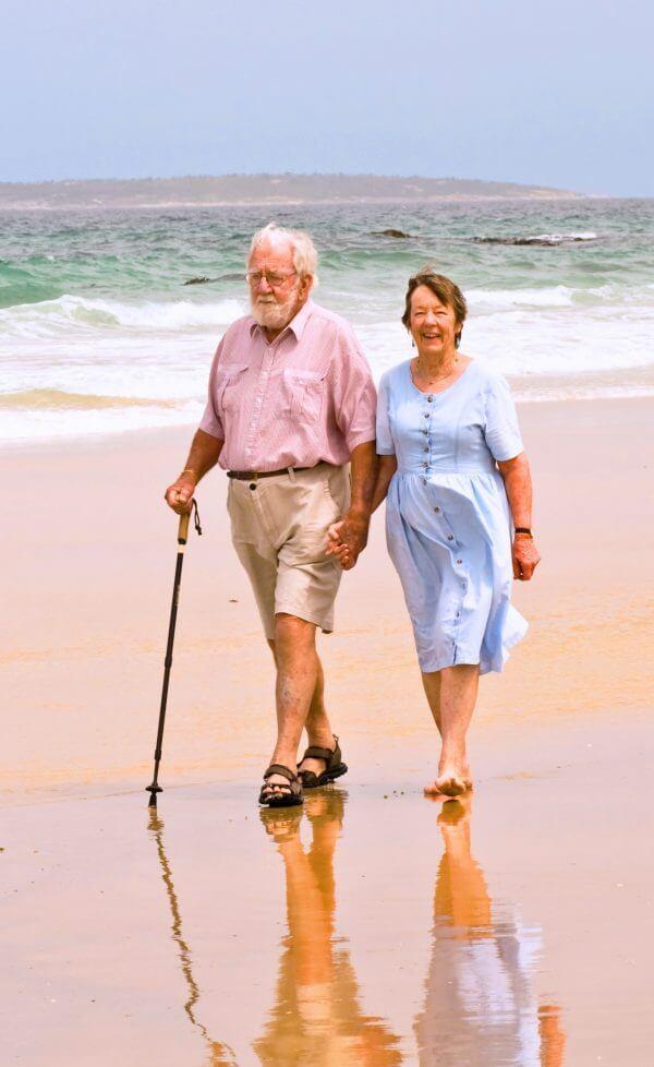 an elderly couple walking on the beach
