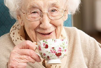elderly woman smiling while hold a cup of tea