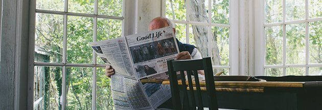 an elderly reading a newspaper